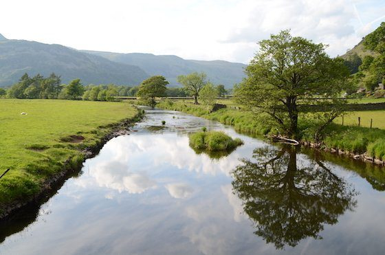 The placid Godrill Beck as it flows through Patterdale, with trees reflected in the water