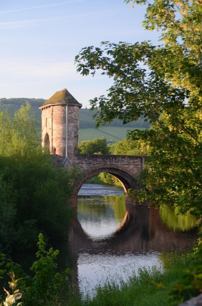 Bridge reflected in the river with defensive tower and gate into Monmouth on the Offa's Dyke Path