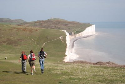 South Downs Way: Three trekkers with small rucksacks jogging on the Seven Sisters cliffs