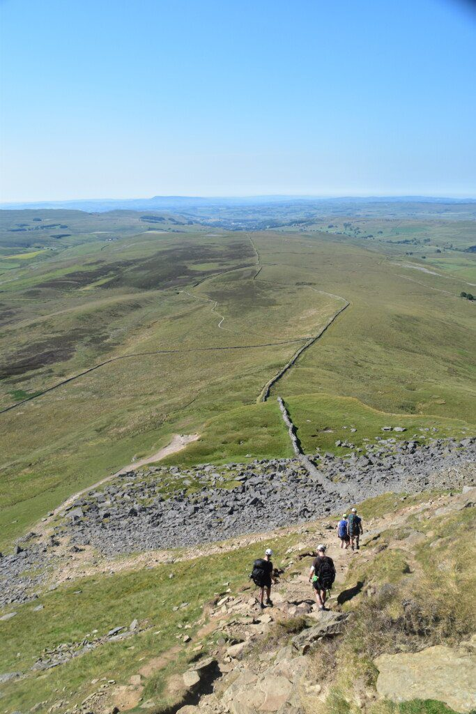 Four trekkers heading down the slopes of Yorkshire's Pen-y-Ghent on a cloudless day