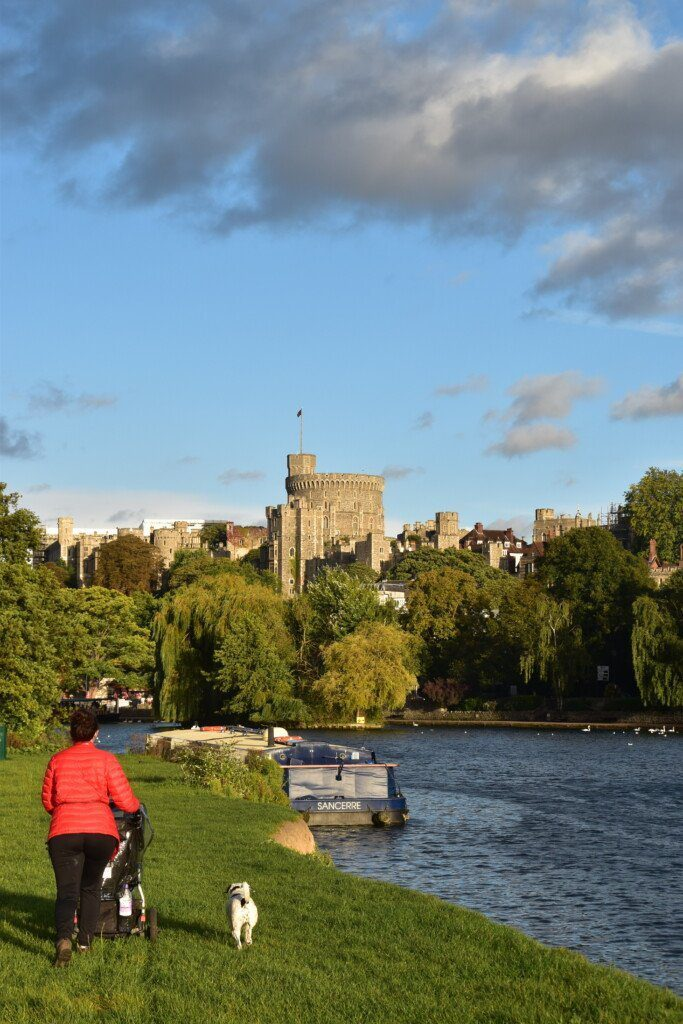 Hiker with pram marches through a field along the banks of the River Thames with Windsor Castle in the distance.