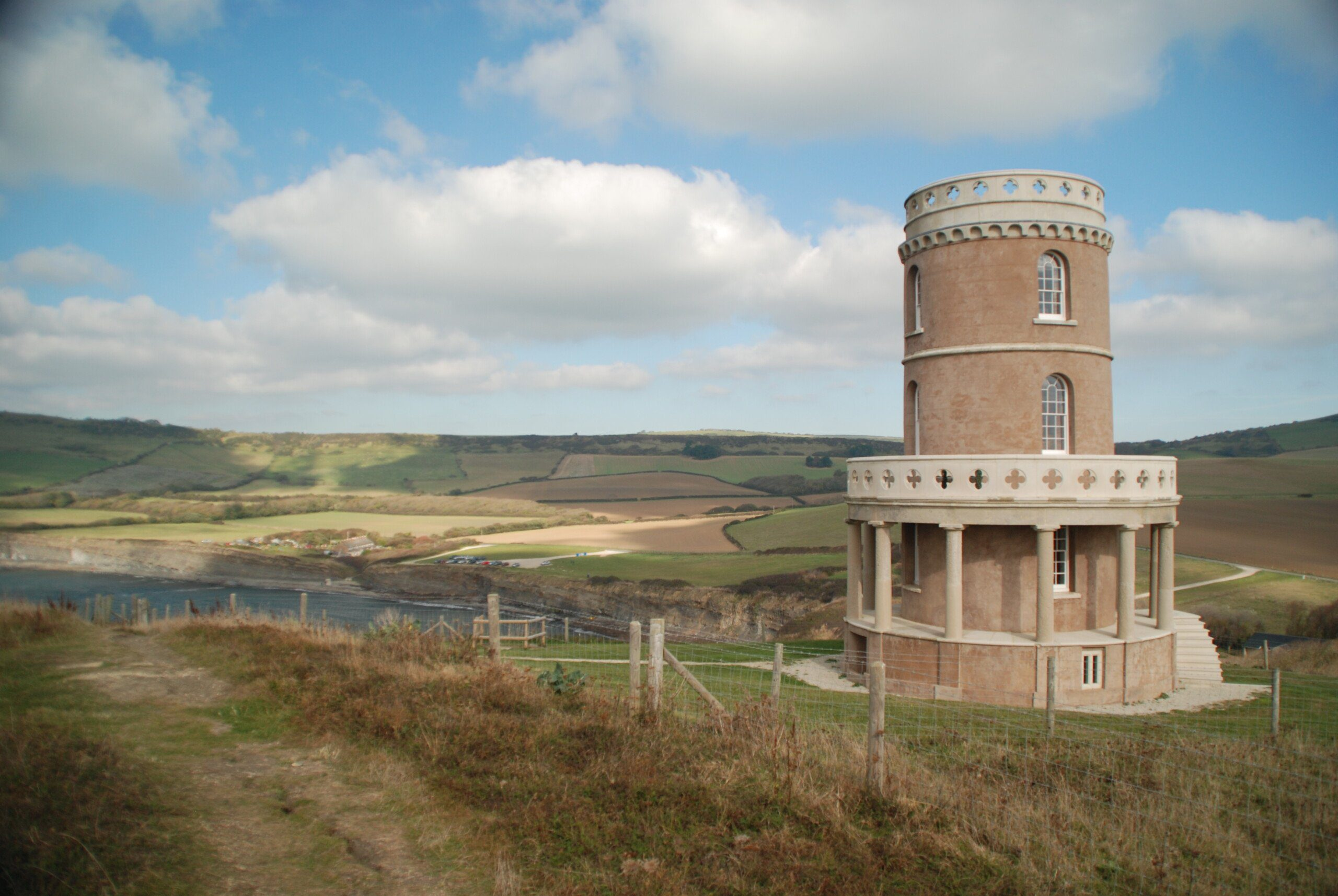Small brick Clavell Tower overlooking fields and sea of Kimmeridge Bay, on the final lag of the South-West Coast Path
