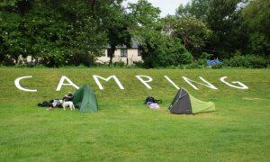 Two tents in front of large letters in the grass spelling 'Camping' at Porlock