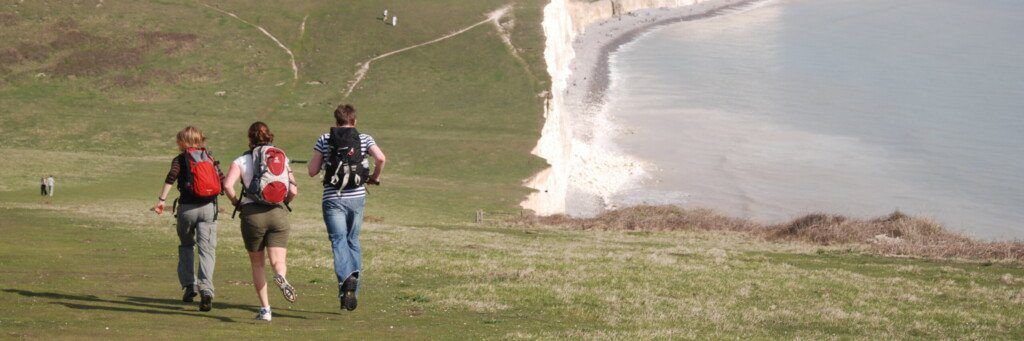 Three hikers on the Seven Sisters at the end of the South Downs Way, jogging downhill away from the camera