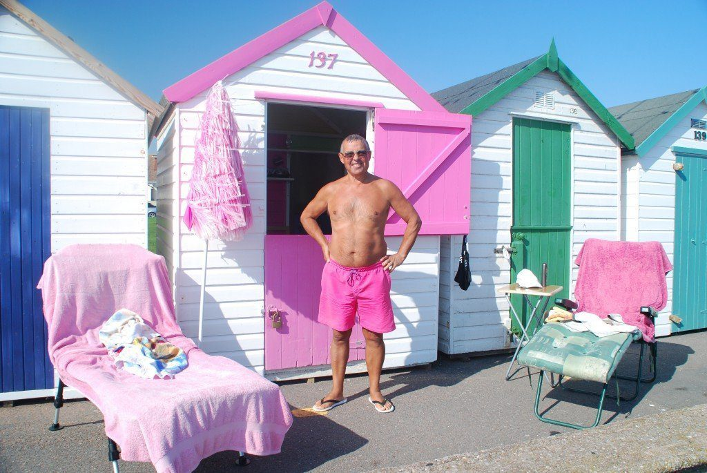 Man in pink trunks by pink beach hut with pink towels, Paignton, on the South-West Coast Path