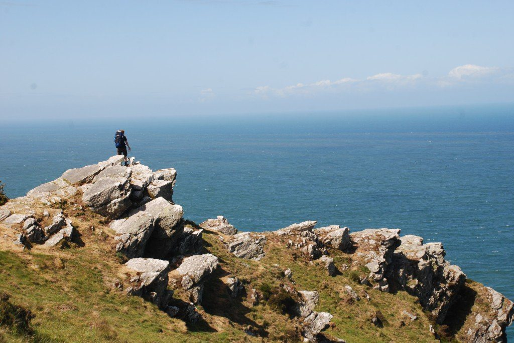 South-West Coast Path, Exmoor North Devon, hiker looks out to see from rocky outcrop