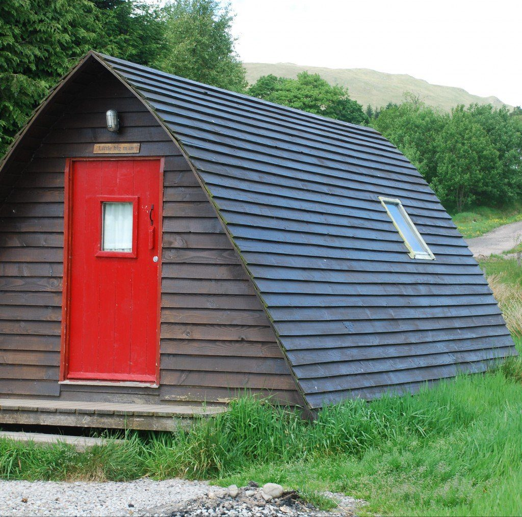 Wooden A-frame 'hut' with red door on the West Highland Way