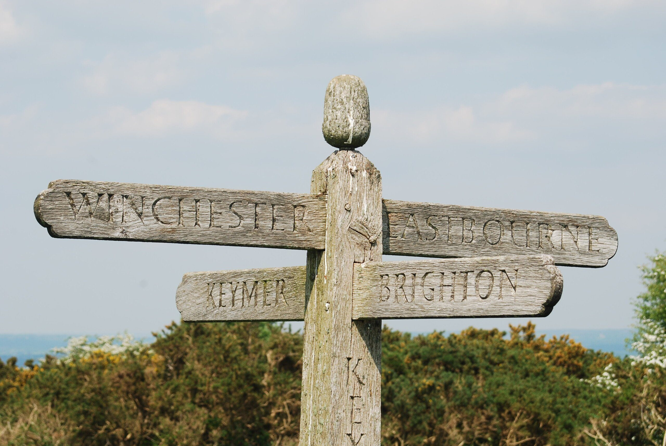 South Downs Way: Old wooden signpost pointing the way to Keymer, Brighton, Winchester and Eastbourne