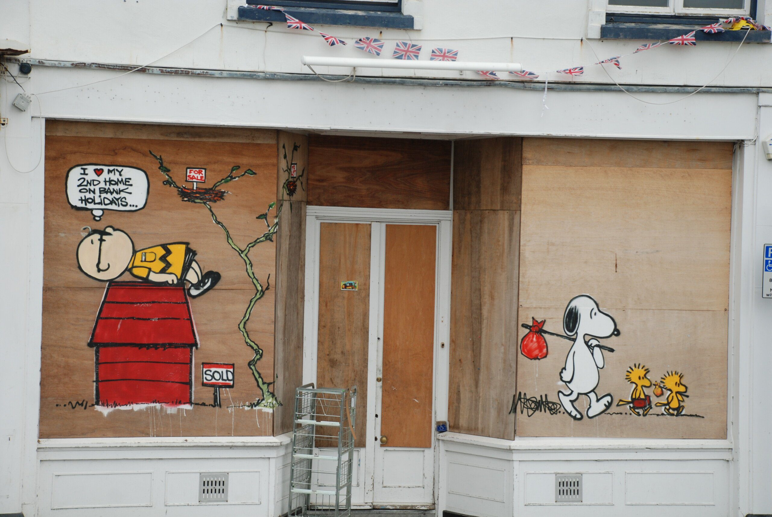 A boarded-up shopfront with grafitti of Charlie Brown lying on Snoopy's kennel, and Snoopy walking away with two Woodstocks. Charlie Brown is saying 'I love my 2nd home on Bank Holidays'