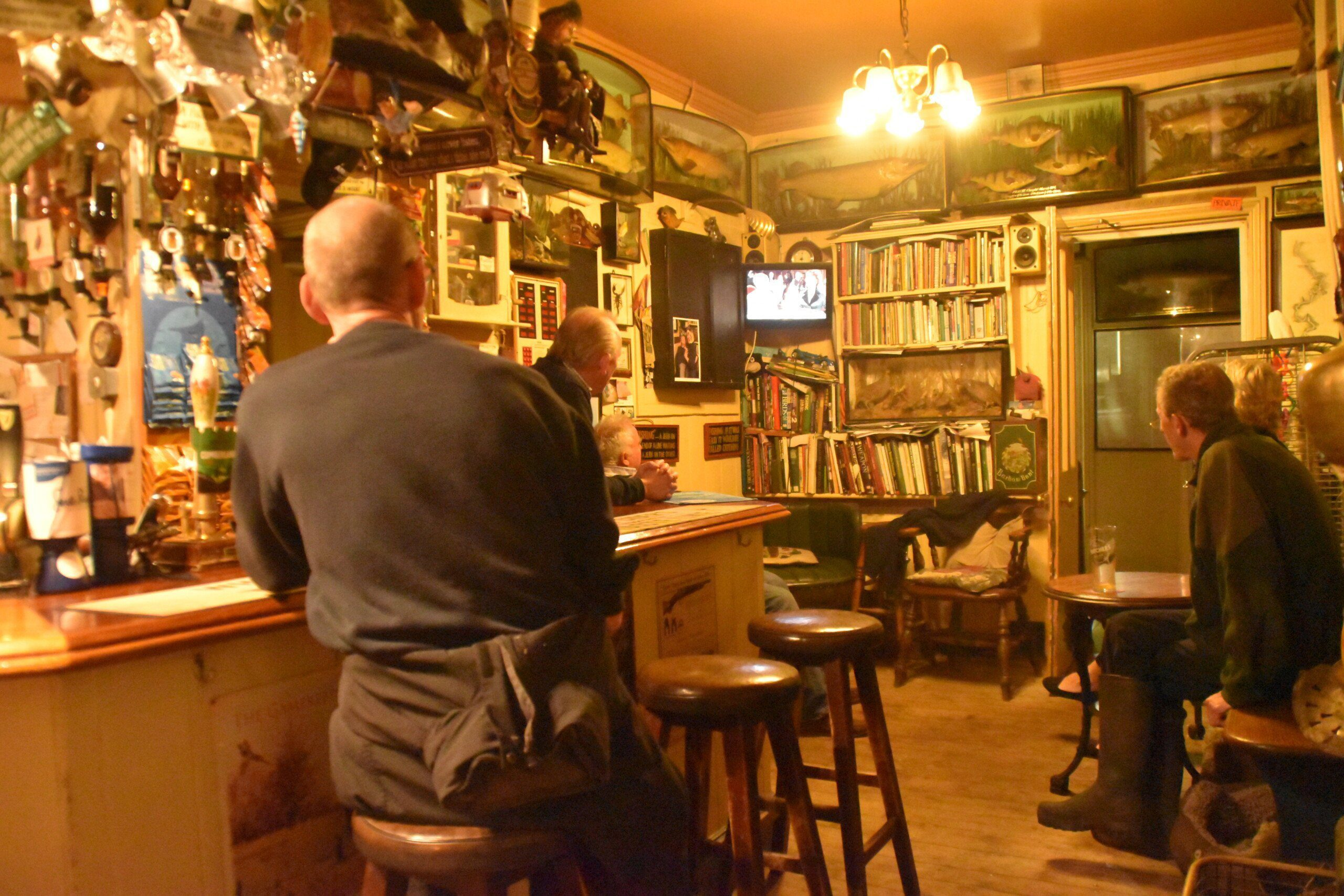 Two regulars and the landlord of The Flowerpot pub at Aston watching the television