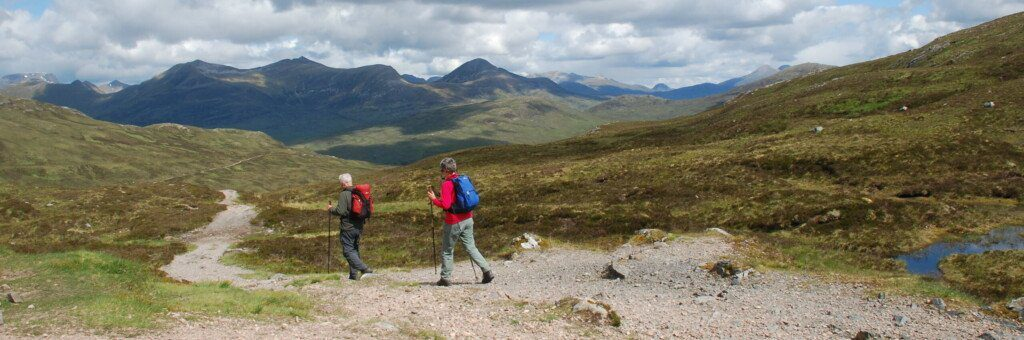 Two hikers with Scottish Highlands in the background on the West Highland Way.