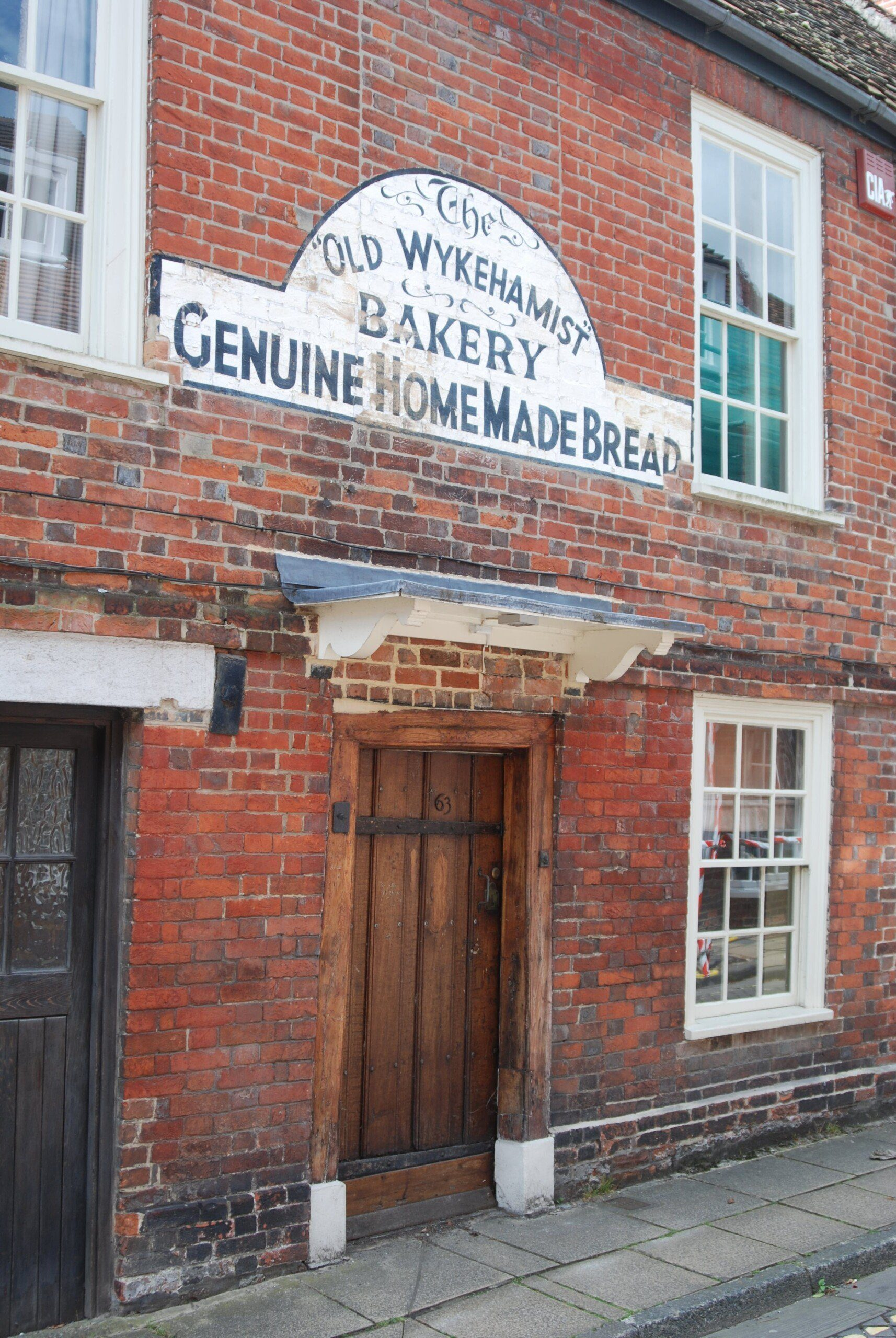 Brick terraced building with sign painted on it 'The Old Wykehamist Bakery Genuine Home Made Bread'