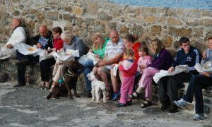 Group of seated diners on the harbour arm at Coverack eating fish and chips from paper