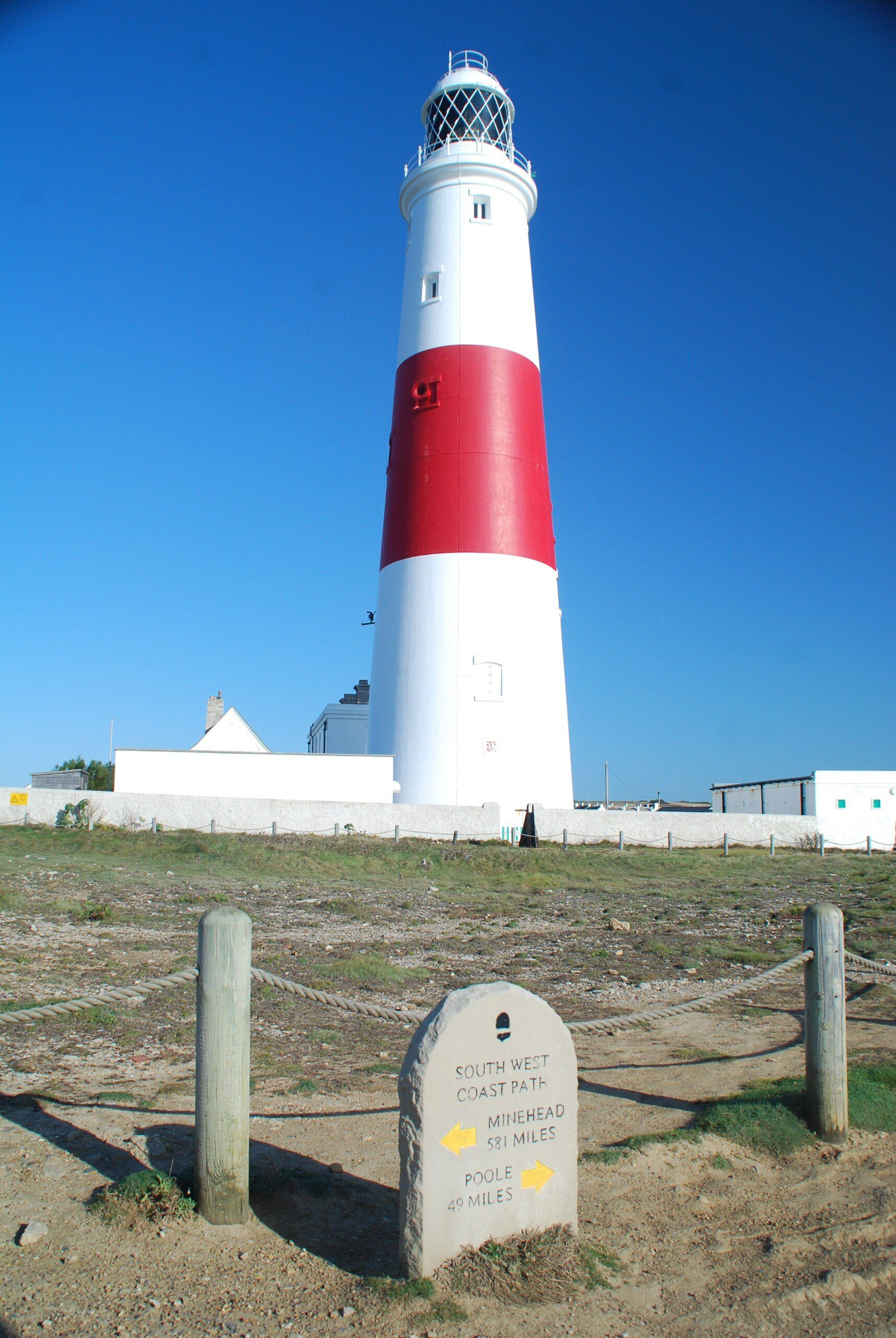 Red and white lighthouse with South-West Coast Path stone sign in foreground.