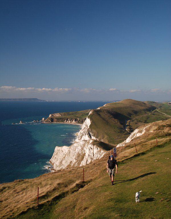 Man walks with dog on Dorset coast path on chalky cliffs