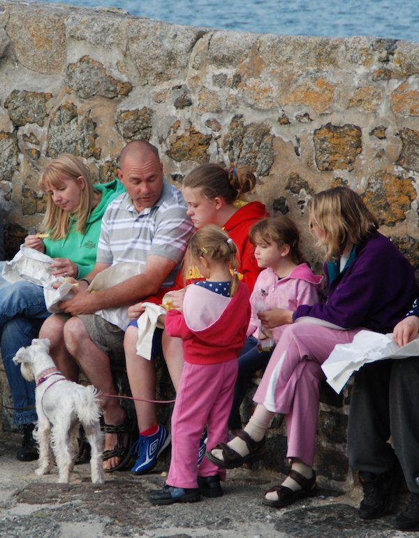 The best food on any trek can be found in Cornwall, as here on the Lizard where a row of people sit and eat fish and chips