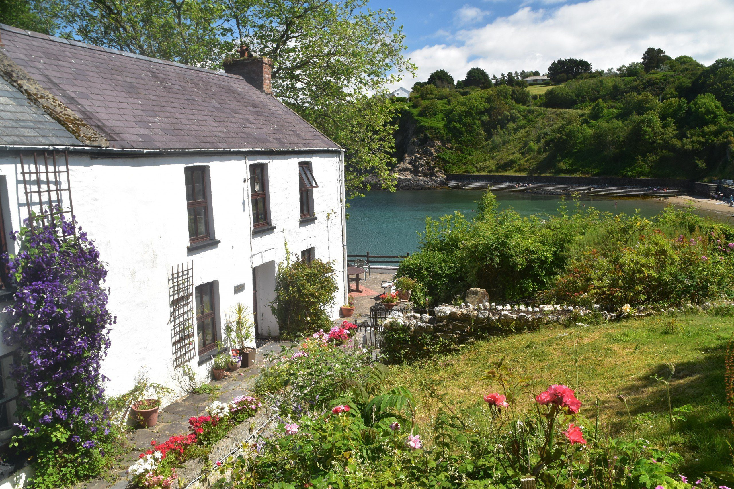 White cottage by the sea at Brynhenllan with flower-filled garden, south of Newport
