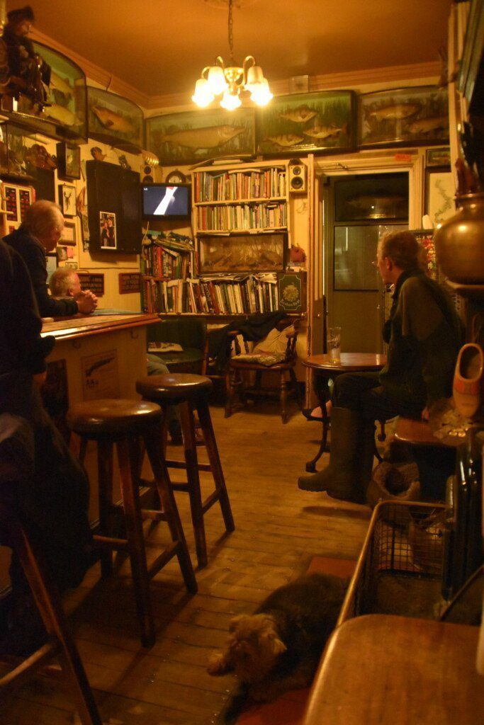 Three men watching a small television in the corner of a cosy, book-lined pub, the Flowerpot Inn, Aston, on the Thames Path.