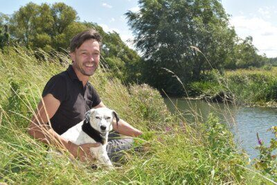 Author Henry Stedman with Daisy sitting by the Thames on the National Trail