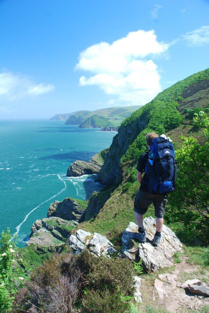 Lone hiker with big blue rucksack stares out over a turquoise sea from a rocky outcrop in North Devon