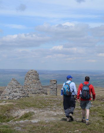 Two hikers walk away from camera past several large piles of stones known as the Nine Standards Rigg