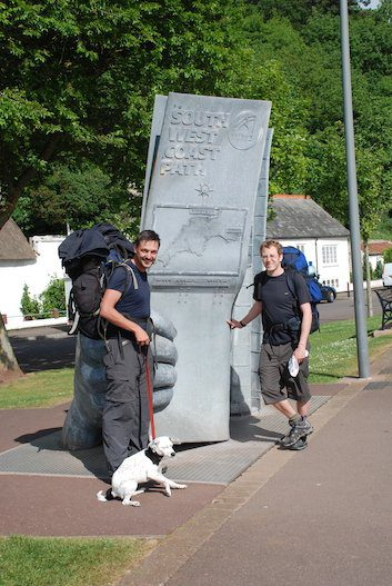 Two hikers plus dog by monument marking start of South-West Coast Path, at Minehead.