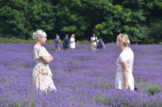 Two women facing each other in the lavender fields of Mayfield