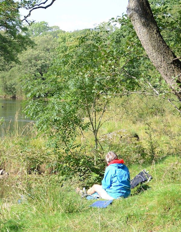 Novice hiker sits on grass by river