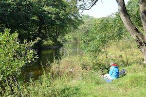 Beginner hiker sits by the River Wharfe on the Dales Way